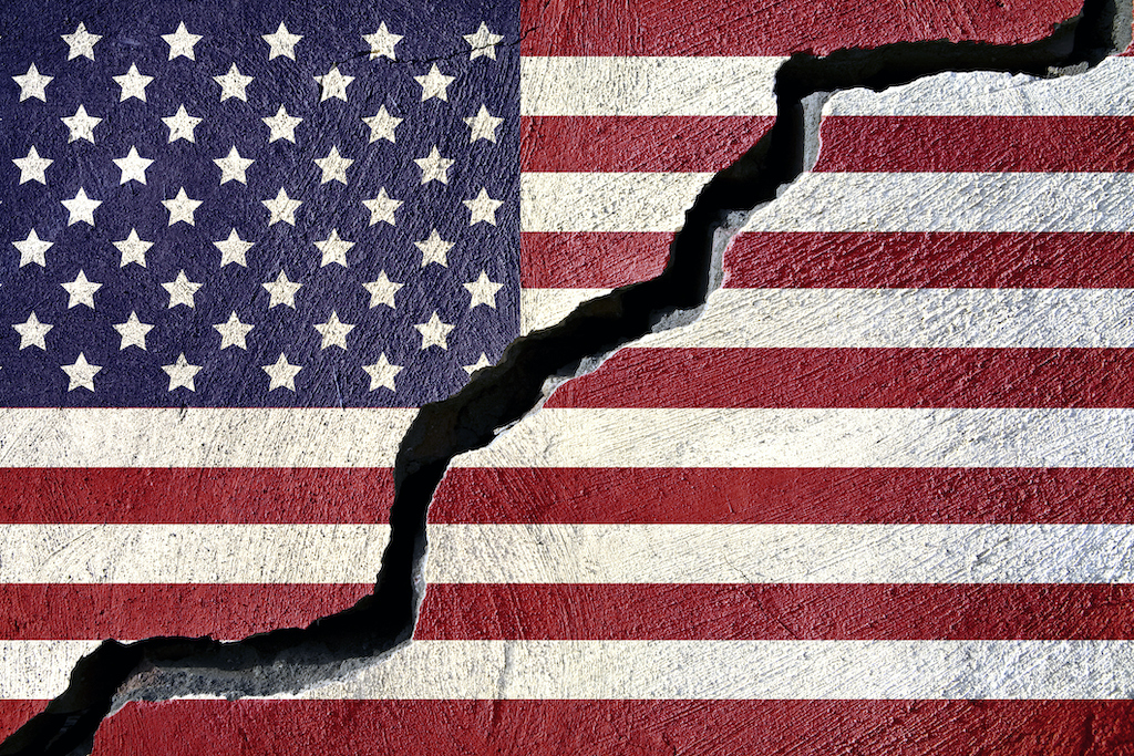 Concept American Flag on Cracked Background (Jorge Villalba/GettyImages Plus from https://www.theamericanconservative.com/dreher/a-divided-country/)